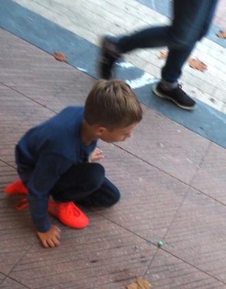 boy playing marbles Ribadesella 816.JPG